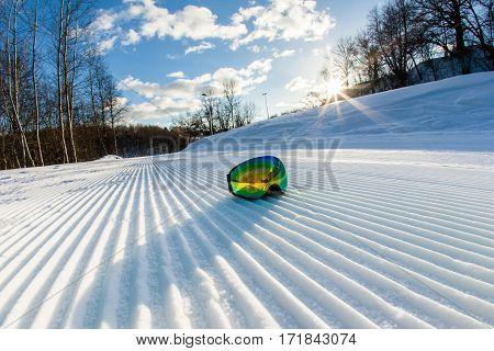 Unbroken ski slope, goggles and blue sky