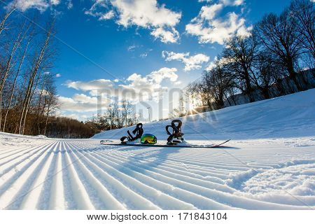 Unbroken ski slope, snowboard, goggles and blue sky