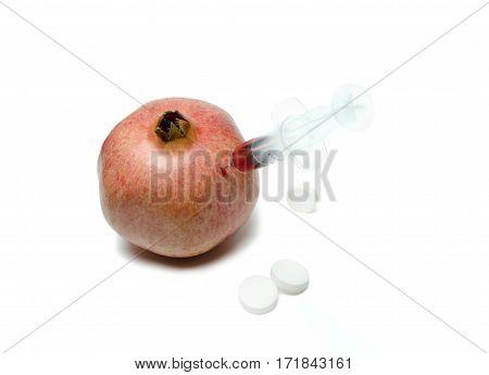 fresh garnet with syringe and white pills on the white background