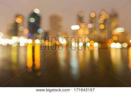 Blurred bokeh light city office building with reflection night view abstract background