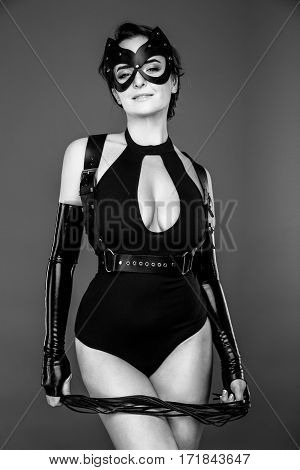 beautiful young sexy woman in bodysuit, baldric and black cat mask, posing in studio