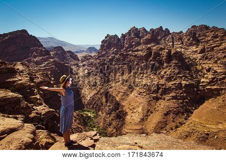 Photo Freedom traveler woman standing with raised arms enjoying amazing mountain landscape. View from Petra to Wadi Araba desert. Hipster young girl love travel freedom. Summer vacation. Copy space