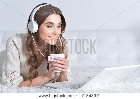 Woman ing headphones listening to musicand drinking tea