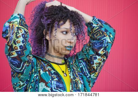 portrait of a teen woman with purple afro hair and blue lips on a pink wall