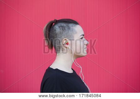 hipster teenager listening to music with strawberry earphones on a pink wall