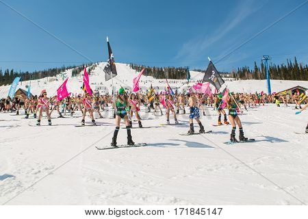 Group Of Young Happy Pretty Women On A Snowboard In Colorful Bikini With Flags.
