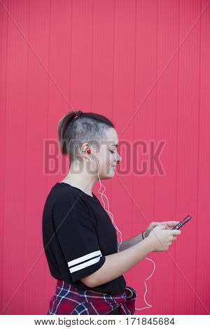 Young woman listening to music with strawberry earphones on a pink background