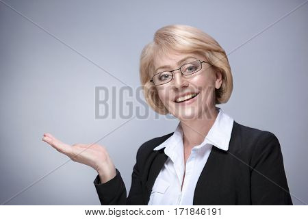 Beautiful Matured Woman happy cheerful caucasian in glasses toothy smile blond studio shot looking at camera. Showing empty copy space on open hand palm for text. Proposing a product. Grey background