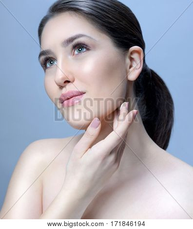 beauty portrait of attractive young  caucasian woman brunette on blue background studio shot skincare face skin applying cream head and shoulders looking up hands neck. fresh looking perfect skin