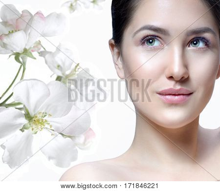 Beauty Spa Woman with Perfect skin Portrait. Beautiful Brunette Spa Girl . Young Caucasian with Fresh looking Skin. Beauty Woman  White background. Looking up. Studio shot. Spring white fresh Flowers