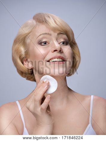 Beautiful Matured Woman Cleaning her Face with cotton discs. Happy cheerful caucasian toothy smile blond. Studio shot. Looking off camera. Face care. Grey background. 50 . Skin care concept