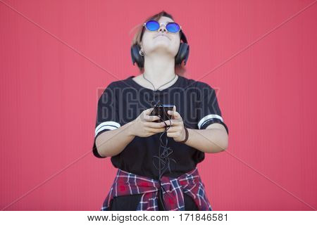 teenager listening to music from her phone isolated on pink background