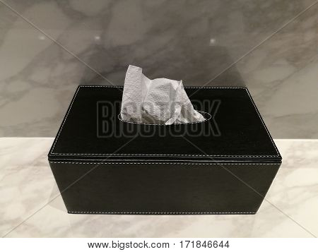 Leather tissue box on marble counter in toilet bathroom with light reflection top view