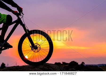 Professional Down Hill Cyclist Resting with Bike on the Rock at Sunset. Close-up image of the Front Wheel. Extreme Sport Concept.
