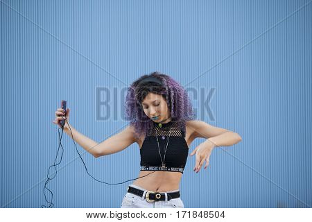 teenager with afro hair listening to music with big headphones