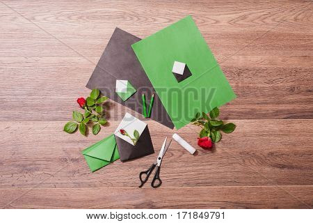 Color paper. Small colored envelopes. Making a greeting card. Workplace designer. Romantic letter. Flower arrangement with stationery items. Grey pencil glue for paper on wooden background. Flat lay