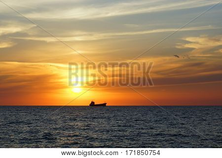 Sunset on the Black Sea. Merchant ship in the sunset background