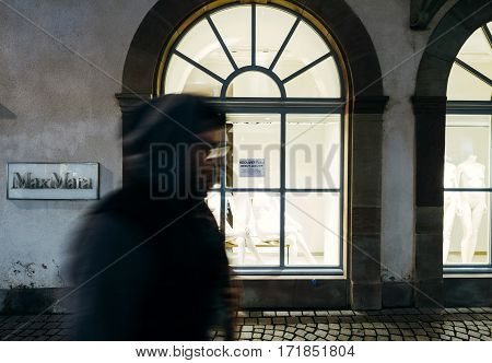STRASBOURG FRANCE - DEC 6 2016: Max Mara Empty fashion store window with two mannequins and silhoueete of man walking at night on the shopping street