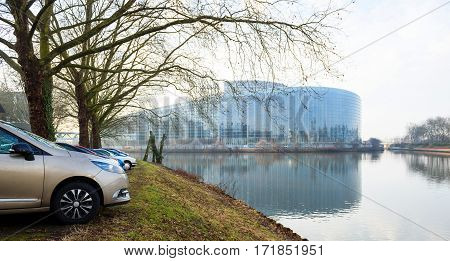 STRASBOURG, FRANCE- FEB 2, 2017: Rows of cars parked in front of Ill river in Strasbourg with the European Parliament building seen in the background