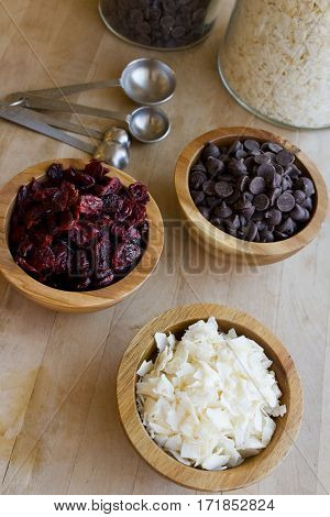 Wooden bowls filled with dried coconut shavings cranberries and chocolate chips.