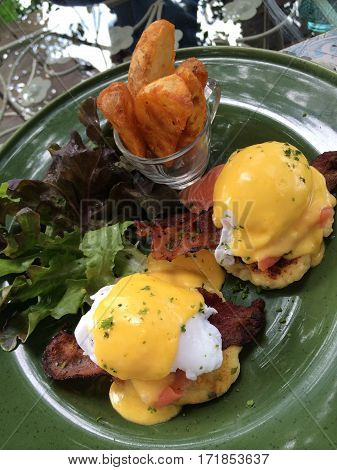 Eggs Benedict with smoked salmon top with fresh herbs and hollandaise sauce serve with green salad and French fries in green plate with blur background and mirror reflect poached egg top view