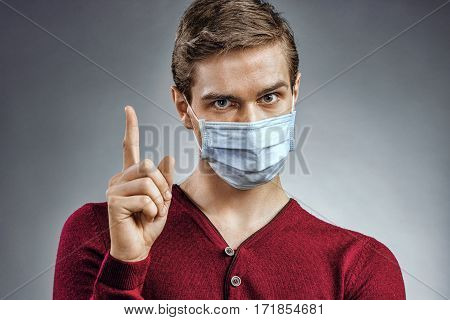Handsome man in protective mask pointing finger up. Health care concept.