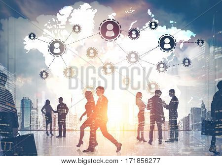 Silhouettes of business people walking against a morning cityscape. There is a world map and a network. Toned image. Double exposure.