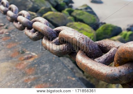 A heavy rusted iron chain by the bay.