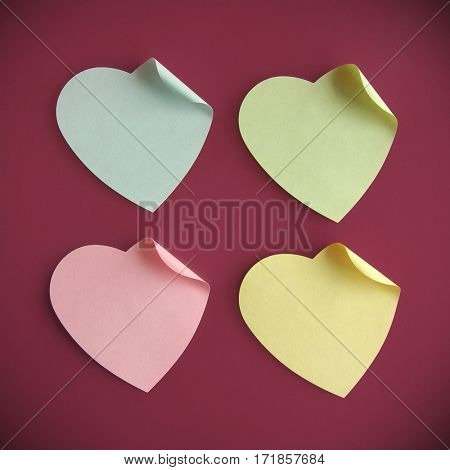 Background of four heart-shaped colorful post its over fainted red