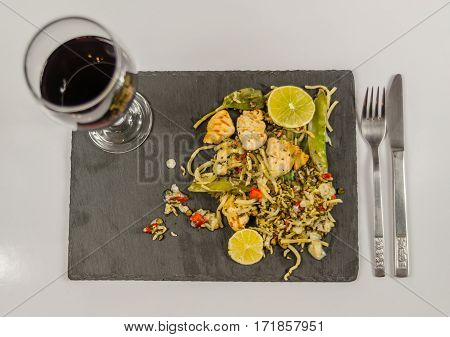 thai chicken with basmati rice coconut sauce on black stone plate with cutlery red wine in a wineglass oriental food