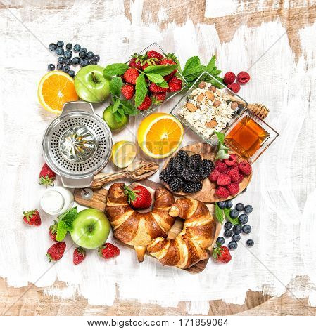Healthy food concept. Breakfast with croissants muesli fresh fruits berries orange apple milk. Top view