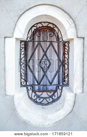 Old window on Murano island, Venice Italy with ornamented metal letter F.
