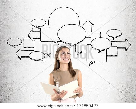 Smiling blond businesswoman is holding a large notebook while standing near a concrete wall with speech bubbles on it. Mock up.
