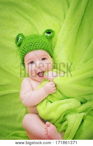 little baby in knitted frog hat on soft blanket on green background