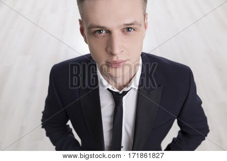 Close up of a blond handsome manager wearing a black suit and tie and a white shirt and looking at the viewer.