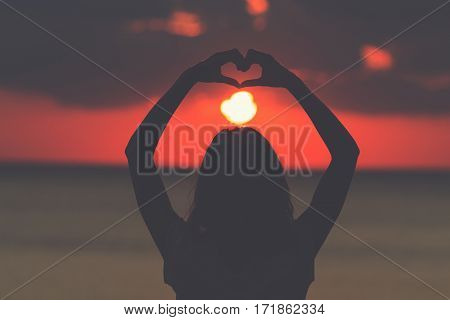 Silhouette of a girl holding a heart-shape with ocean / sea background.