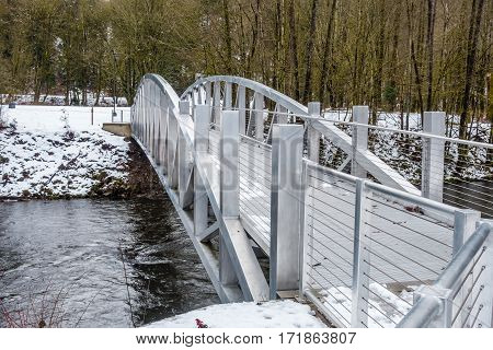 A view of a metal bridge that spans the Cedar River in Renton Washington. Snow covers the bridge and ground.
