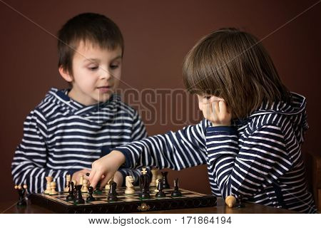 Little Boys, Playing Chess. Smart Kid, Isolated, Playing Chess Agains His Brother