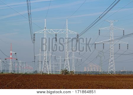 line of electricity pylons and nuclear power plant