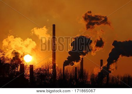 nice orange sunset and steaming steel factory