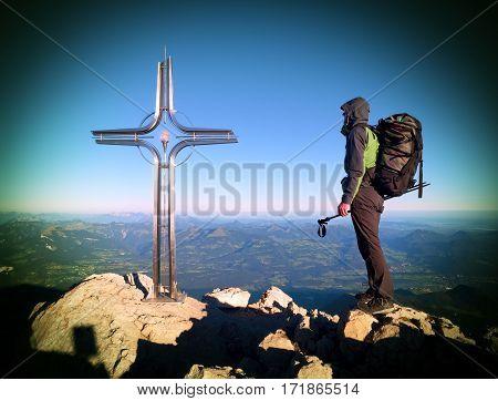 Hiker At Big Crucifix On Mountain Peak. Iron Cross At Alps Mountain Top.