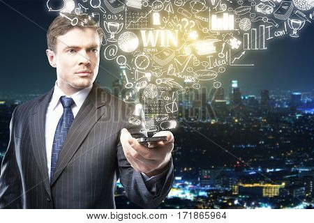 Focused businessman holding cellphone with abstract business sketch on night city background. Technology concept