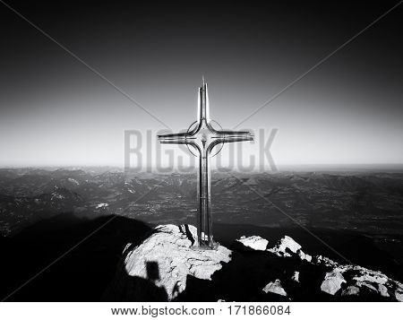Cross with semi-precious stone raised at mountain summit in Alps. Sharp peak. Daybreak Sun in sky. Steel crucifix in memory of victims of mountains. Vivid photo.