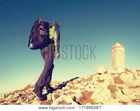 Hiker With Backpack Climbing On Mountain Peak. Summit Stone In Alps
