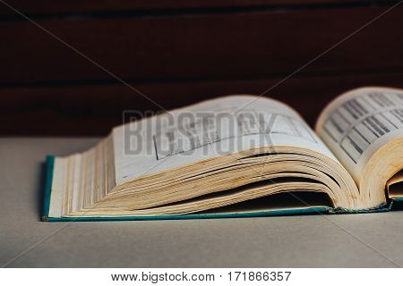 Open book. Dark background . Back to school or library. Copy space. Toned retro image.