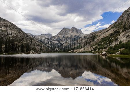 California Sierras reflected in Barney Lake, clouds with a hint of blue sky