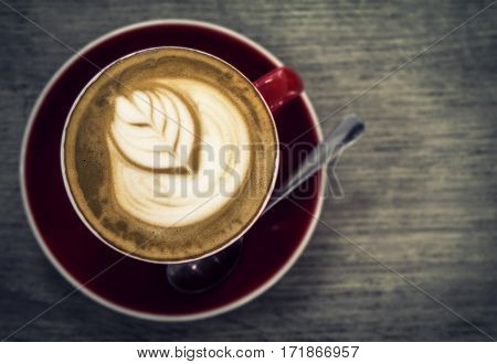 Artistic latte art in a red cup