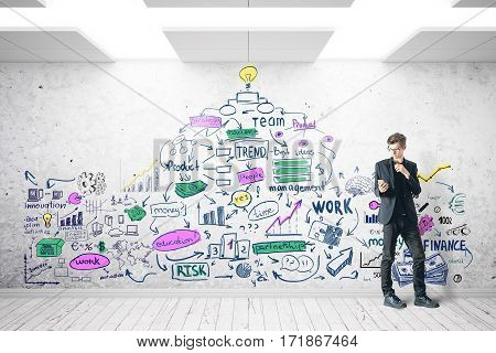 Young businessman using smartphone in concrete room with colorful business sketch. Entrepreneurship concept. 3D Rendering