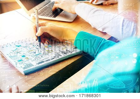 Businesswoman drawing business charts in spiral notepad at workplace. Filtered image