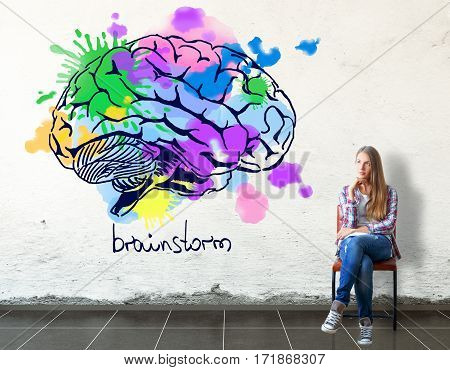 Thoughful european girl sitting on chair in concrete room with bright human brain sketch on wall. Creative thinking concept. 3D Rendering